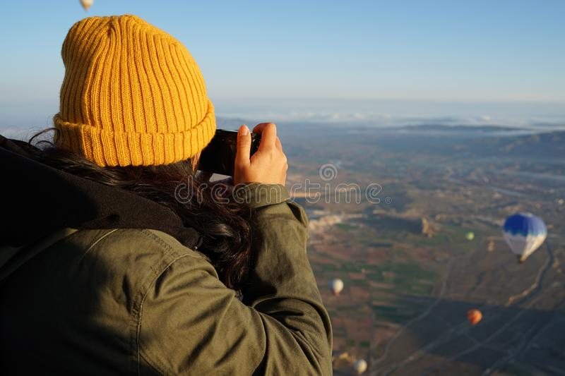 Asian woman traveler taking photo of the balloon in the air with Goreme beautiful landscape. Asian woman traveler wearing yellow wool hat taking photo of the stock photos
