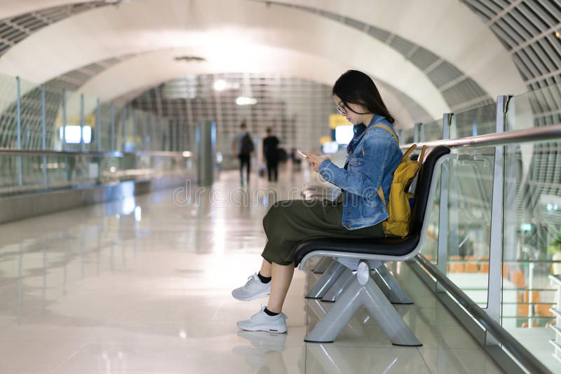 Asian woman traveller using smart phone, waiting for boarding at the airport's terminal stock photo