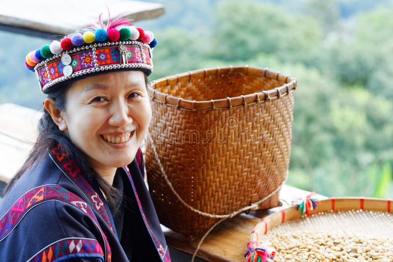 Asian woman in the tribe dress be smile happy with coffee seed. Asian woman in the tribe dress be smile and happy with coffee seed royalty free stock photography