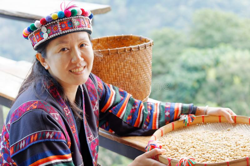 Asian woman in the tribe dress be smile happy with coffee seed stock photo