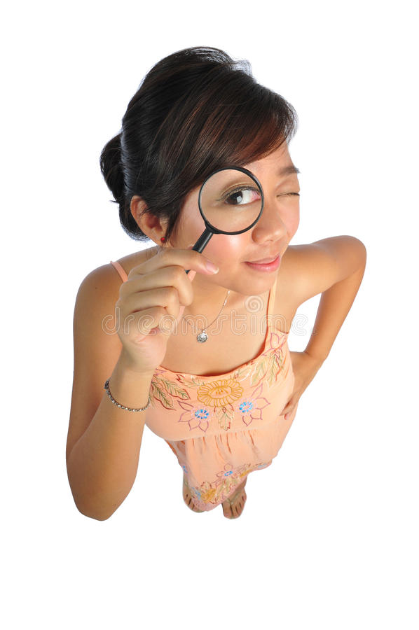 Asian Woman trying to see with magnifying glass. Beautiful young Asian Woman picture taken from the top to give a big doll head effect royalty free stock photography