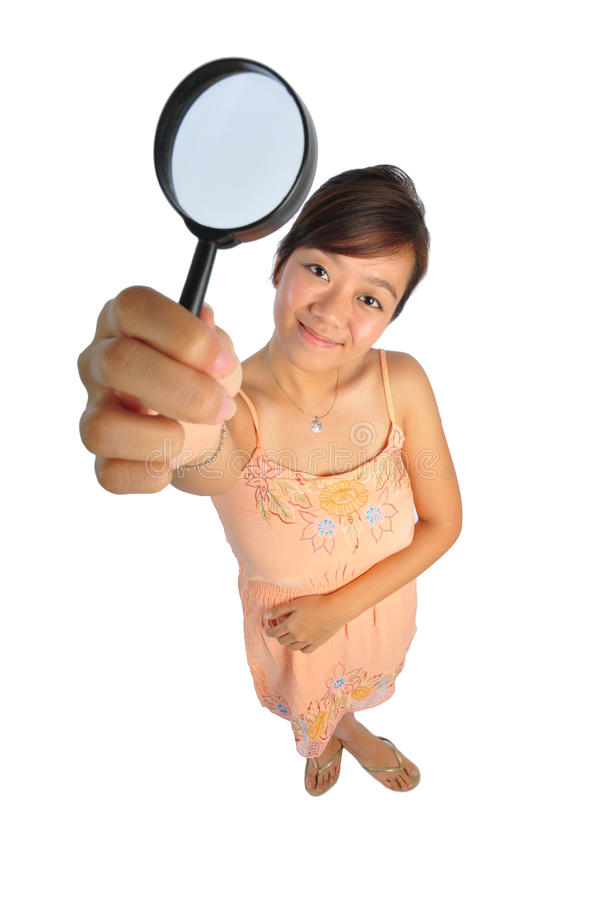 Asian Woman trying to see with magnifying glass. Beautiful young Asian Woman picture taken from the top to give a big doll head effect royalty free stock images