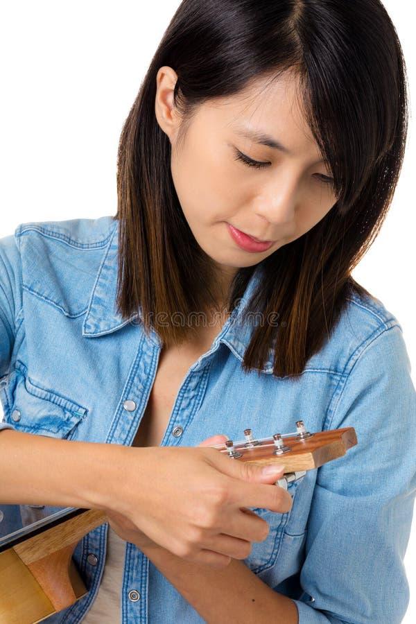 Asian woman tunning ukelele stock photos