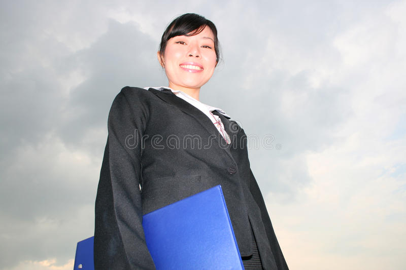 Asian woman under a cloudy sky. royalty free stock photography