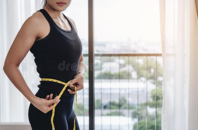 An asian woman use their own waist measurement straps. To control the size and shape of yourself after exercise. stock images