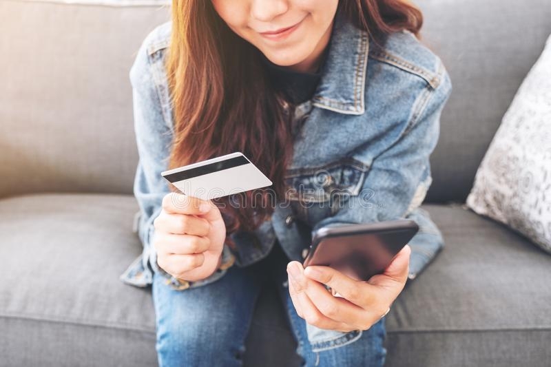 Woman using credit card for purchasing and shopping online on mobile phone. An asian woman using credit card for purchasing and shopping online on mobile phone stock photography