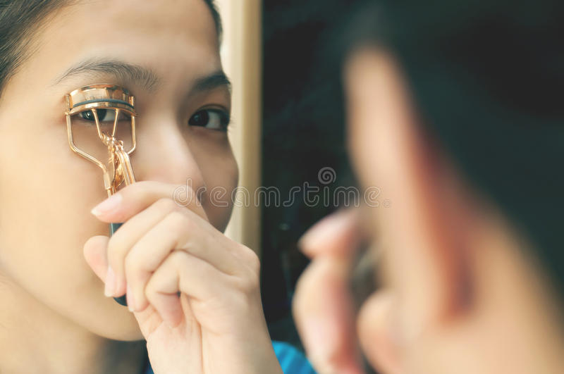 Asian woman is using eyelash curler. Asian girl looking through the mirror stock photography