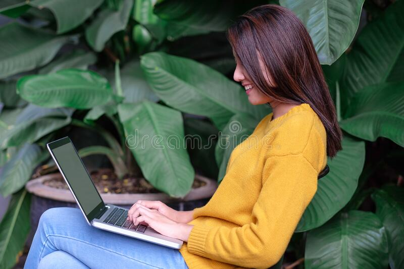 Asian woman using laptop surfing interent and sitting outdoor at home garden.digital age technology lifesytyle.  stock images