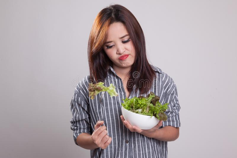 Asian woman very hate salad. Asian woman very hate salad on gray background royalty free stock images