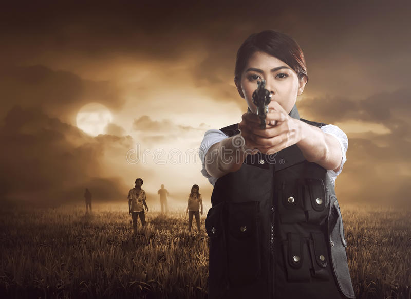 Asian woman with vest holding pistol on the meadow stock photo