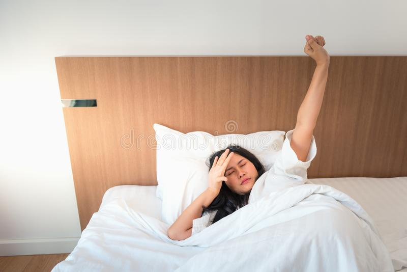 Asian woman waking up in bedroom and stretching her arms in the royalty free stock photography