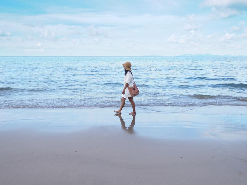Asian woman walking alone on sand along the beach in the morning stock image