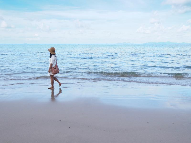 Asian woman walking alone on sand along the beach in the morning stock photos