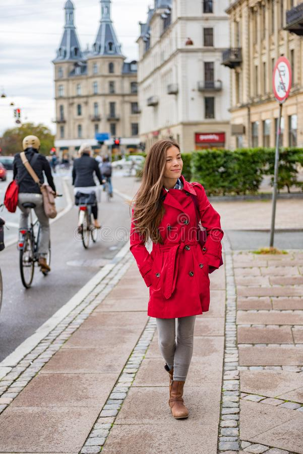 Asian woman walking in red fashion trench coat relaxing outside in Copenhagen city street, Denmark. Europe travel tourism tourist royalty free stock image