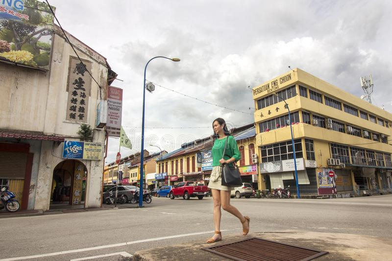 Asian woman walking on the street of historical town of Bentong. 2017 Dec 05 Pahang, Malaysia - an attractive asian lady tourist walking on the street of Bentong stock image