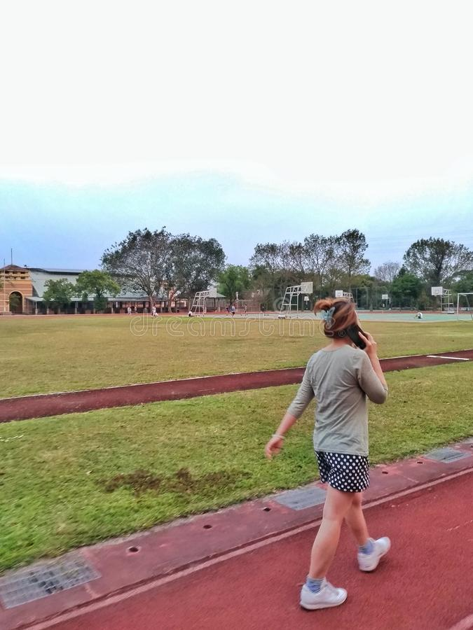 An asian woman is walking on the track of a school, and talking on the phone while walking. An asian woman is walking on the track of a school, and talking on royalty free stock image
