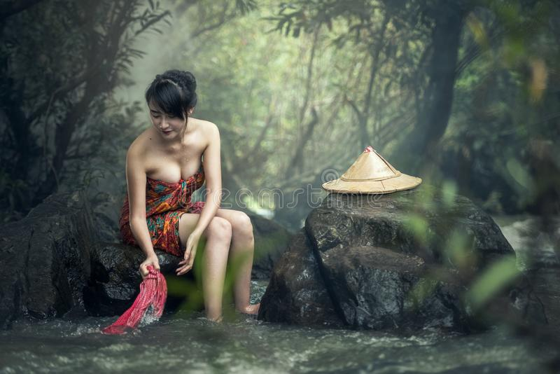 Asian woman washing clothes in stream stock image