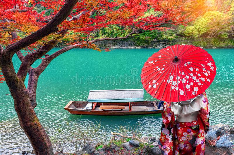 Asian woman wear Kimono and watch The leaves change color. Boatman on the Katsura River on both sides is full of beautiful. Colorful trees stock photo