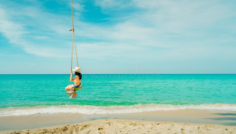 Asian woman wear swimwear and hat swing the swings at sand beach  and looking beautiful tropical paradise sea and sky on sunny day royalty free stock photo