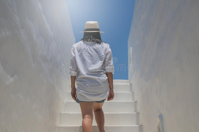 Asian woman wear white shirt and weave hat walking up on concrete stairs. royalty free stock images