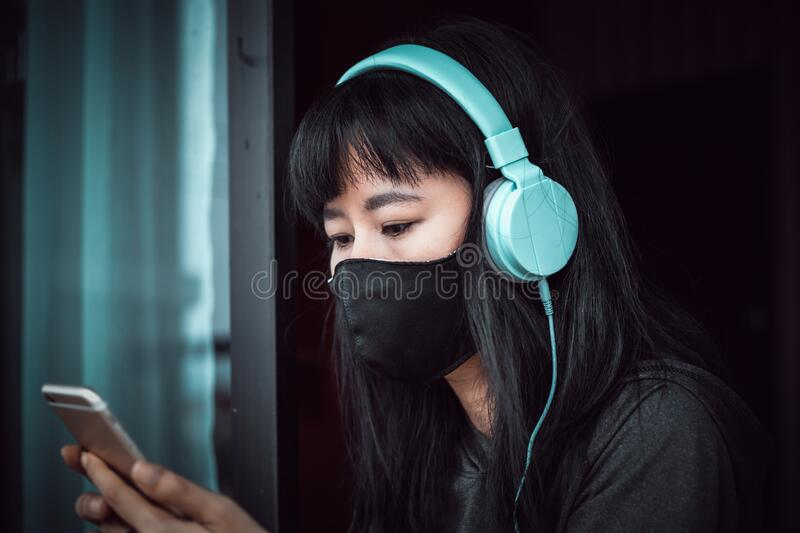 Asian woman staying home for self-quarantine and social distancing in coronavirus or Covid-2019 outbreak situation. Asian woman wearing a black face mask and stock photo