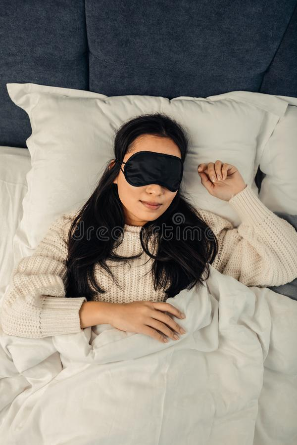 Asian woman wearing black sleeping mask lying in bed royalty free stock photography