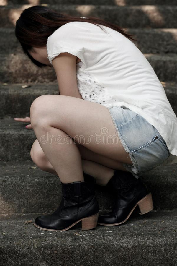 Asian woman wearing boots crouching on cement steps. Asian woman wearing boots crouching down on rough textured cement steps with shorts royalty free stock photography