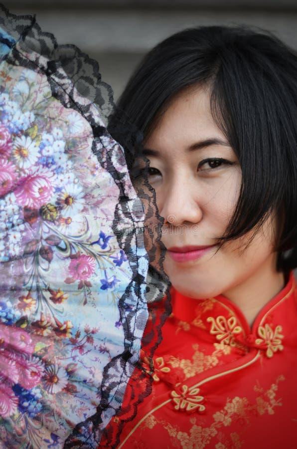 Asian woman wearing a cheongsam with folding fan stock photos