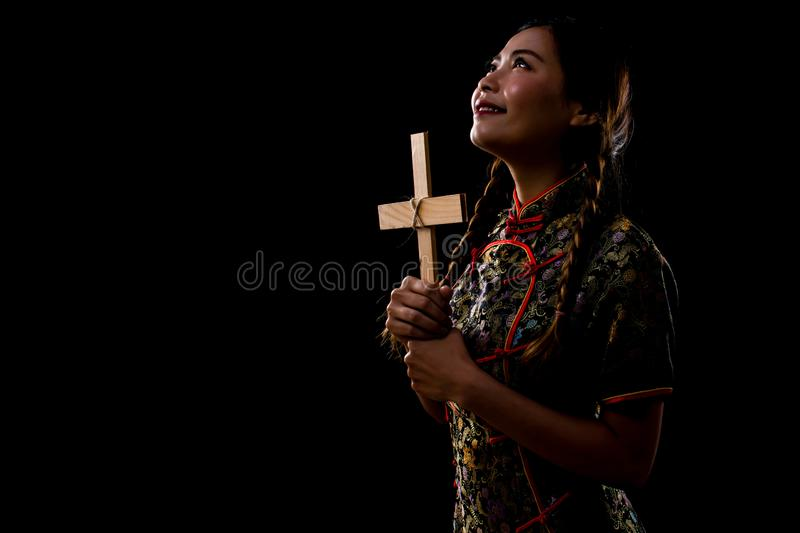 Woman wearing chinese dress holding a cross royalty free stock image