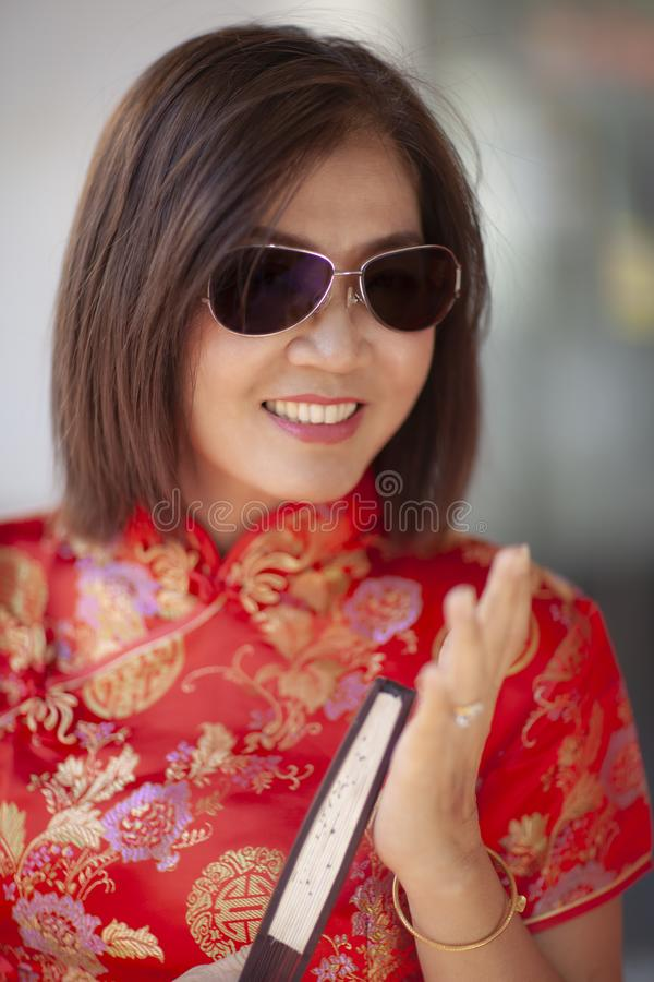 Asian woman wearing chinese tradition clothes with chinese  bamboo fan toothy smiling face in yaowarat street china town of royalty free stock photo