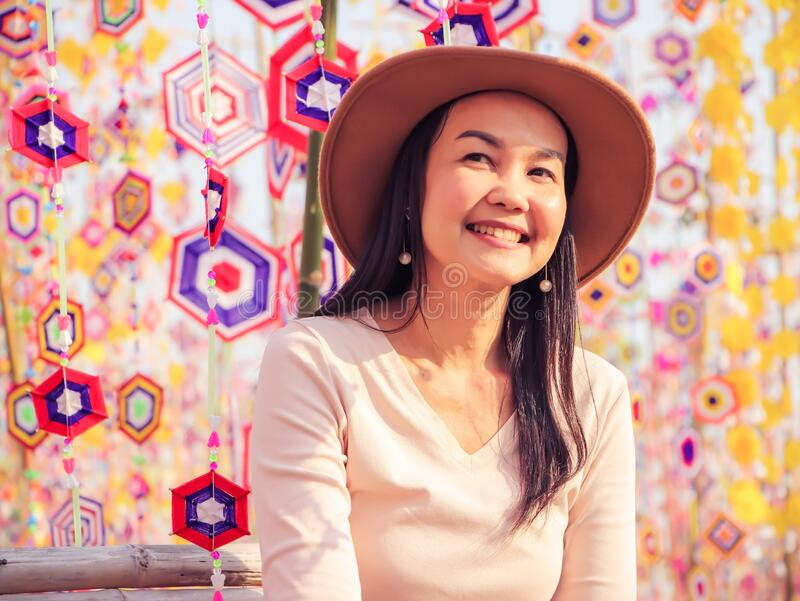 Asian woman wearing hat , sitting among colorful tung flag traditiona north-eastern Thai craft smiling and looking away. Beautiful Asian tourist woman wearing stock image
