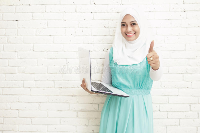 asian woman wearing hijab holding laptop and giving thumbs up royalty free stock photos