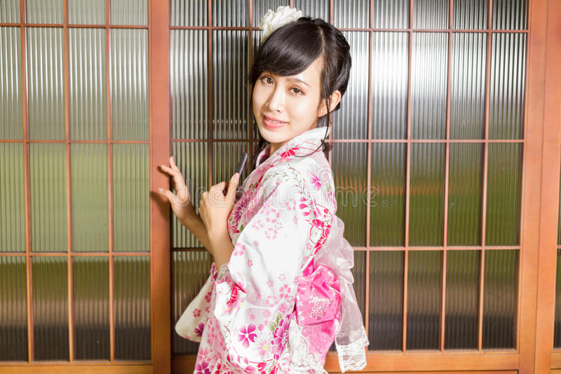 Asian woman wearing a kimono in front of Japanese wooden windows stock photography