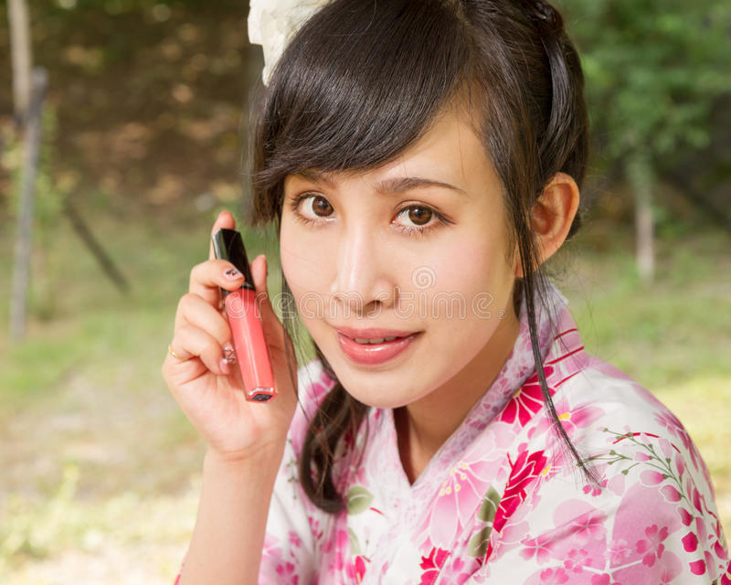 Asian woman wearing a kimono holding up lip gloss stock images