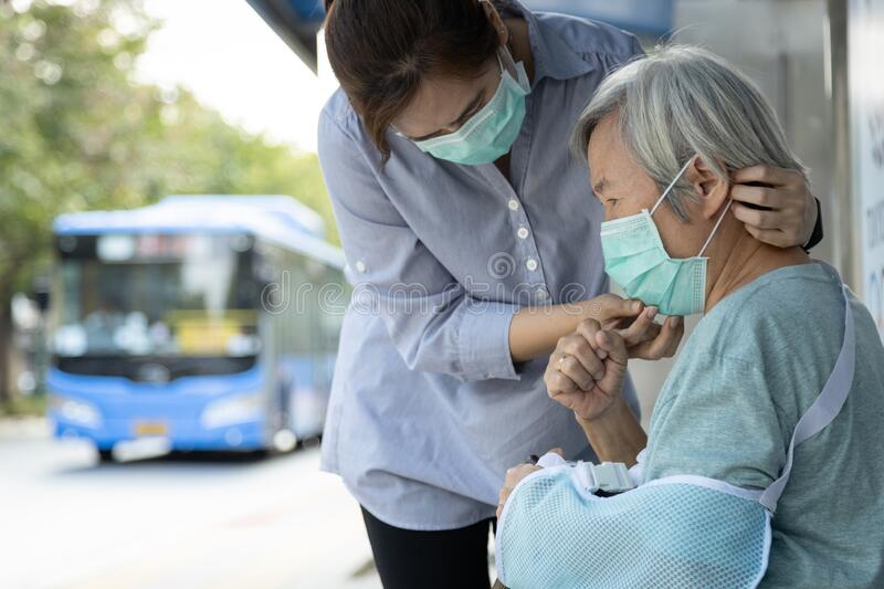 Asian woman wearing medical face mask for senior person because sick female elderly with cough and fever,prevent spread of germs royalty free stock photography