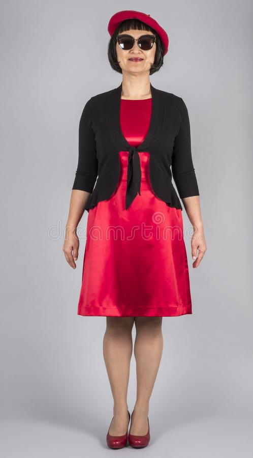 Asian Woman Wearing Red Satin Dress and Matching Red Beret Hat and Red Leather Pumps 1. Asian Woman Wearing Red Satin Dress with a Black Cardigan, Red Beret and stock photo