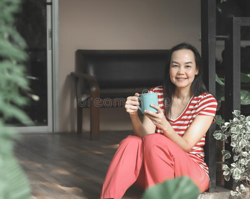 Asian woman wearing red stripe t-shirt sitting in balcony wiht house plants decoration ,holding cup of coffee .smiling at camera. Happy Asian woman wearing red royalty free stock photos