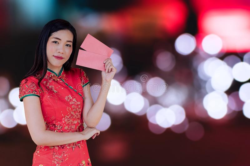 Asian woman wearing red traditional dress holding red pocket with the chinese new year festival background stock photography