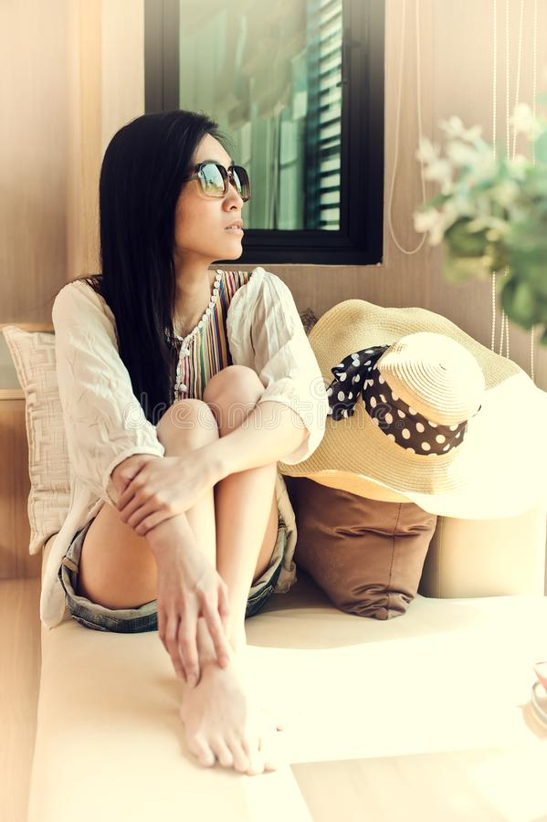 Asian woman wearing sunglasses and looking out the window in vintage style. Portrait of lovely asian young woman dressed in royalty free stock photos