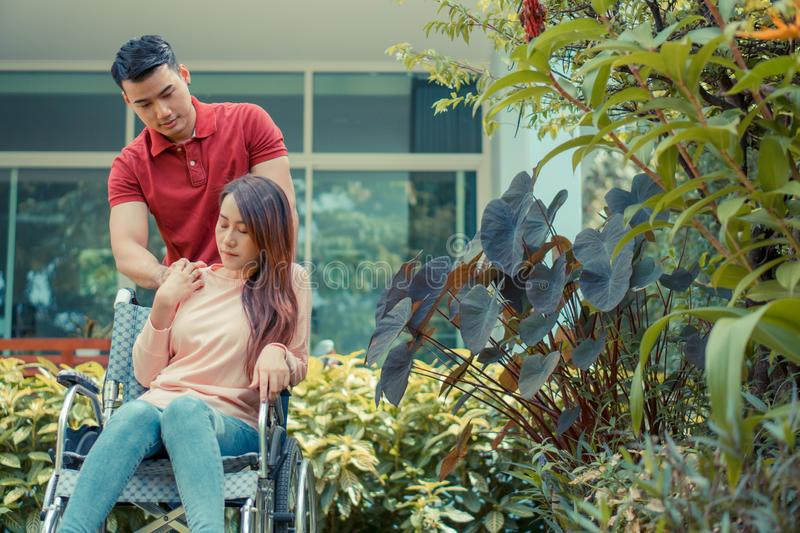 Asian woman in a wheelchair and Unhappy and painful. A Man standing behind the wheelchair and is encouraging his wife, whose feet stock photo