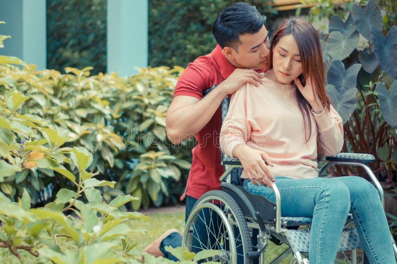 Asian woman in a wheelchair and Unhappy and painful. A Man standing behind the wheelchair and is encouraging his wife, whose feet royalty free stock photos