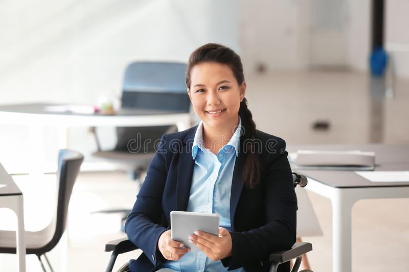 Asian woman in wheelchair working with tablet PC in office royalty free stock image