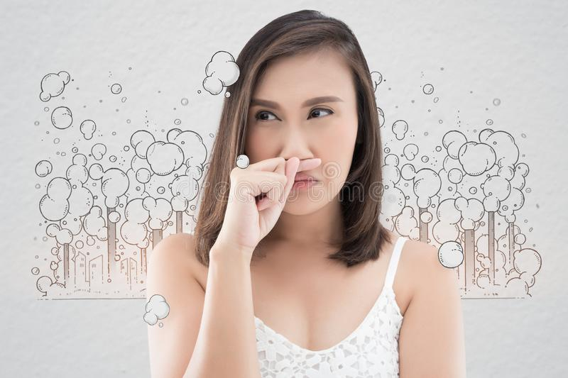 Asian woman in white dress catch her nose because of a bad smell royalty free stock image