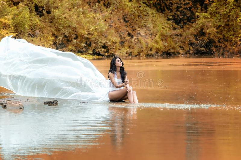 Asian woman with white dress relaxing and sitting at tropical exotic river with turquoise amazing color water in beautiful autumn stock photo