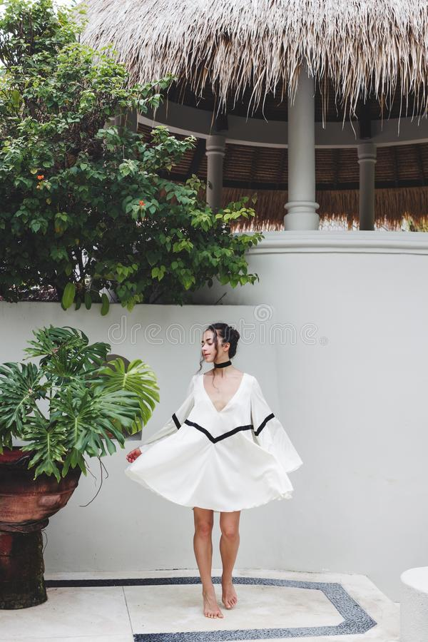 Asian woman in white light tunic, barefoot. Casual style, tropical garden. Asian woman with black curly hair enjoying in private villa in Canggu. Wearing white stock images