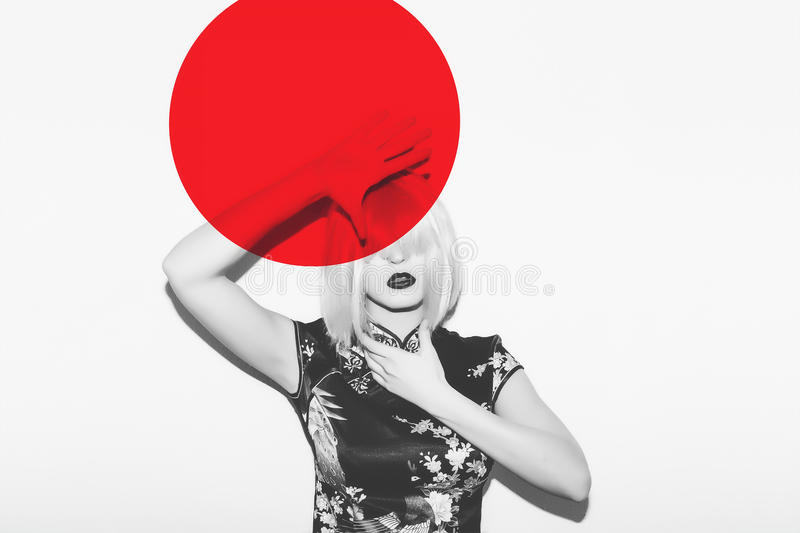 Asian woman in wig hide from hot red sun. Beautiful japanese geisha sakura blossom clothes against red sun design. Asian woman in wig hide from hot red sun royalty free stock images