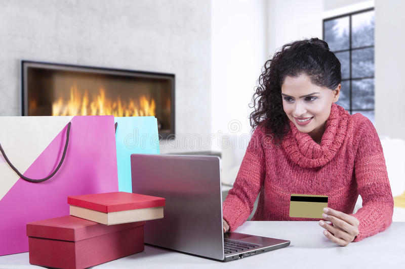Asian woman with winter wear shopping online. Young indian woman smiling happy while using credit card and laptop for shopping online with shopping bags on desk royalty free stock photos