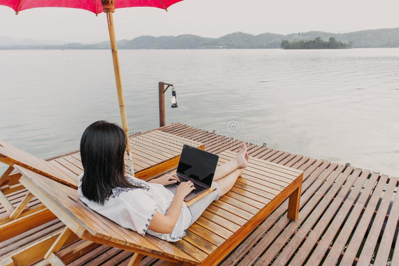 Woman work on her laptop and admire the beautiful lake stock images
