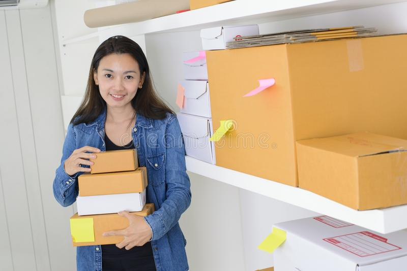 Asian woman work at home office checking order ready to mailing or shipping.  stock photos