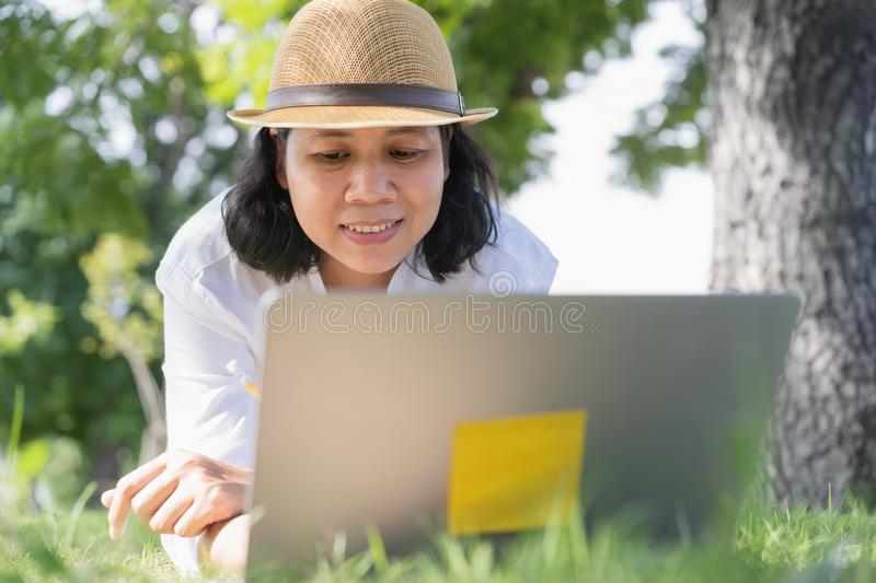 Asian woman work using a laptop while lying on green grass in a public park,  lifestyle business concept. Asian woman work using a laptop while lying on green royalty free stock image